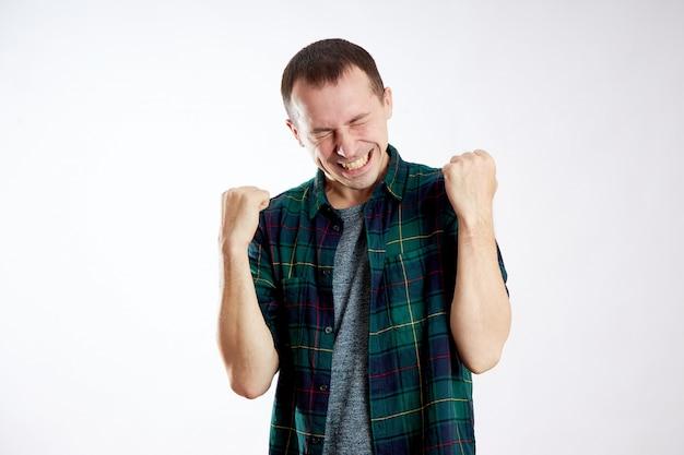 Sukces to radość i szczęście. człowiek jest szczęśliwy, zwycięstwo. szczęśliwa twarz faceta jest izolowana