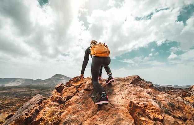 Sukces turysta kobieta z plecakiem na szczycie góry, patrząc na panoramę.