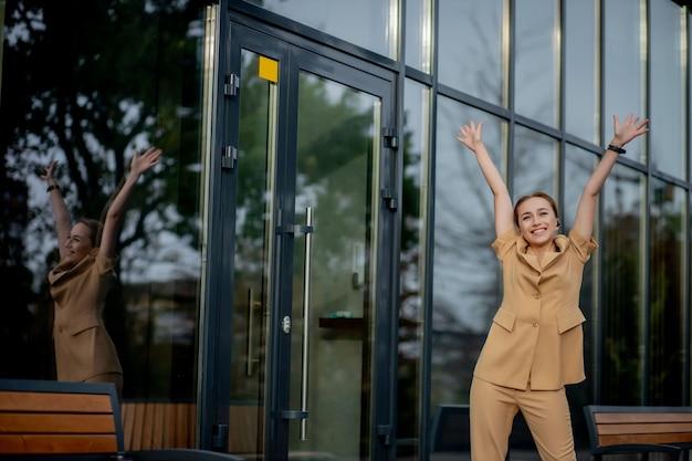 Sukces w biznesie - szczęśliwa młoda kobieta biznesu świętuje osiągnięcia kariery zawodowej obiema rękami przed budynkiem biurowym.