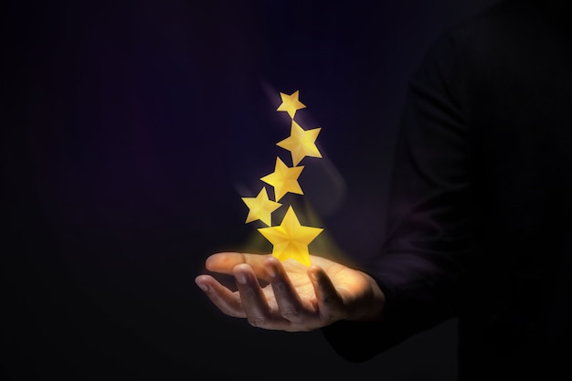 Sukces w koncepcji talentów biznesowych lub osobistych. gest dłoni ze złotymi pięć gwiazdkami
