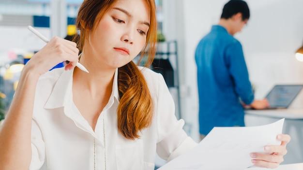 Sukces wykonawczy z azji młoda bizneswoman smart casual wear rysowanie, pisanie i używanie pióra za pomocą cyfrowego tabletu, myśląc o procesie pracy inspiracji i szukania pomysłów w nowoczesnym biurze domowym.