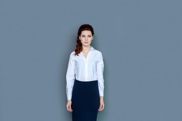 Sukces zawodowy. inteligentny ładny pewny siebie businesswoman stojącej na szarym tle i patrząc na ciebie podczas pracy