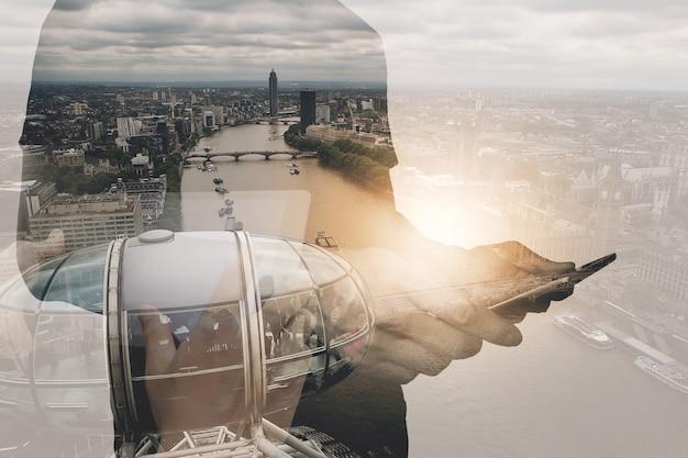 Sukcesu biznesmen używa cyfrową pastylkę z london budynkiem i ogólnospołecznym medialnym diagramem