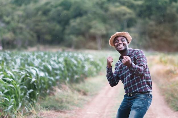 Sukcesu mężczyzna rolnika afrykański stojak przy zielonym gospodarstwem rolnym z kroplą deszczu.
