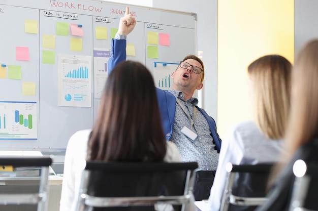Sukcesy biznesmen pokazuje palec na konferencji przed studentami