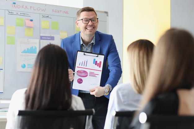 Sukcesy biznesmen pokazuje wykresy na dokumentach na konferencji przed studentami