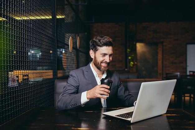 Sukcesy biznesmen pracujący na laptopie podczas przerwy obiadowej w hotelowej restauracji