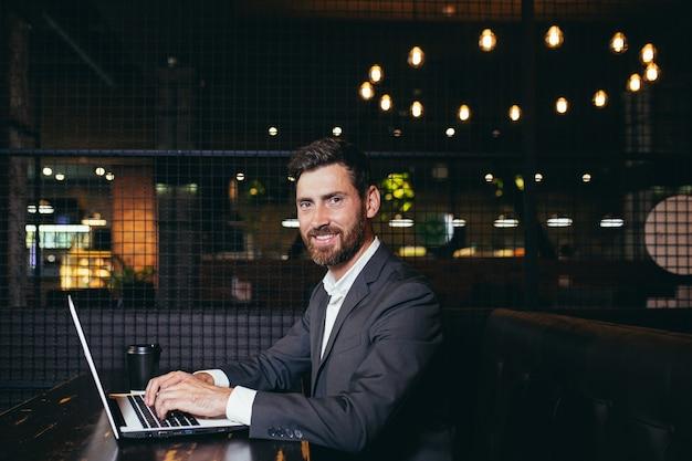 Sukcesy biznesmen pracuje na laptopie podczas przerwy obiadowej siedząc w hotelowej restauracji mężczyzna uśmiechający się patrząc na kamerę z filiżanką kawy