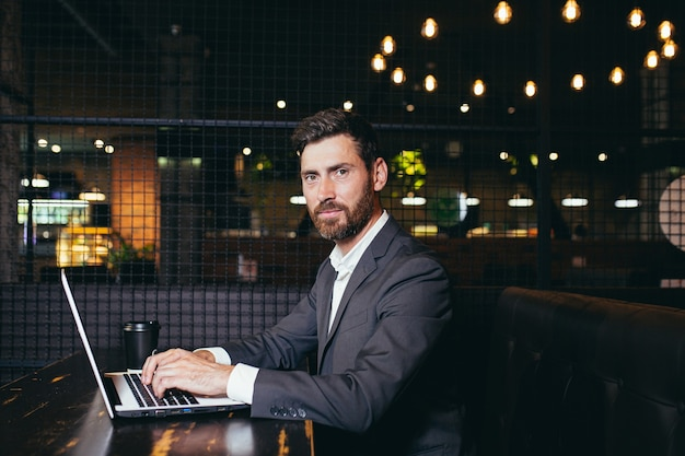 Sukcesy biznesmen pracuje na laptopie podczas przerwy obiadowej siedząc w hotelowej restauracji poważnie patrząc na kamerę z filiżanką kawy