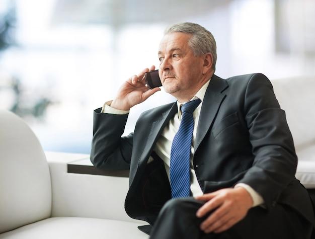 Sukcesy biznesmen rozmawia na smartfonie w biurze