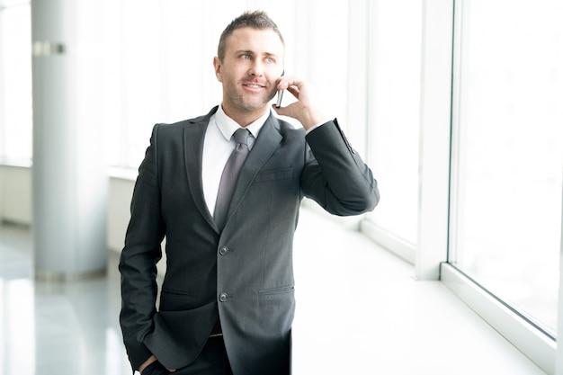 Sukcesy biznesmen rozmawia przez telefon przez okno