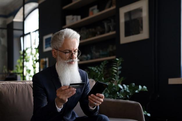 Sukcesy biznesmen siedzi na kanapie w biurze i płaci kartą kredytową ze swoim telefonem komórkowym.