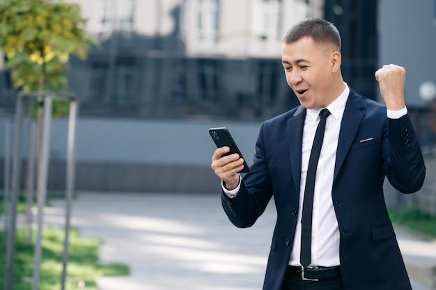 Sukcesy biznesmen świętuje zwycięstwo z telefonu komórkowego na zewnątrz