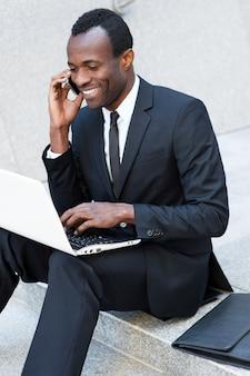 Sukcesy biznesmen. szczęśliwy młody afrykanin w formalnej stroju rozmawia przez telefon komórkowy i pracuje na laptopie, siedząc na zewnątrz klatki schodowej