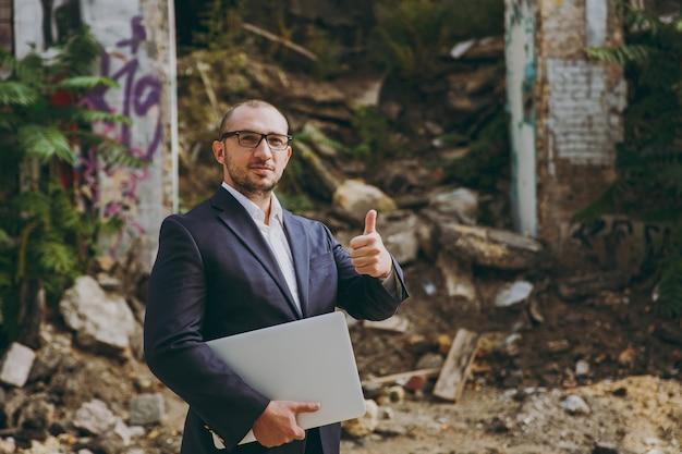 Sukcesy biznesmen w białej koszuli, klasycznym garniturze, okularach. człowiek pokaż kciuk w górę, stoisko z laptopem komputer telefon w pobliżu ruin, gruzu, kamienny budynek na zewnątrz. mobilne biuro, biznes, koncepcja pracy.