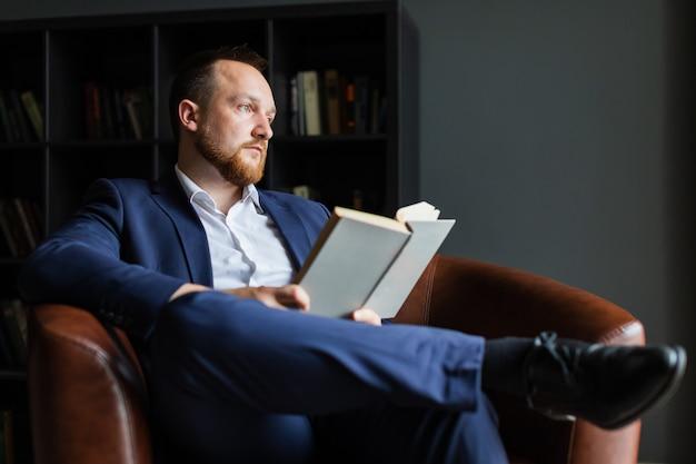Sukcesy biznesmen w garniturze siedzi czytając książkę i zastanawia się.