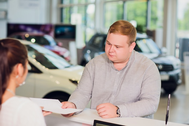Sukcesy biznesmen w salonie samochodowym - sprzedaż pojazdów klientom