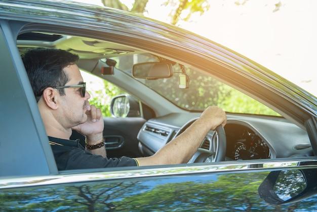 Sukcesy biznesmen w swobodnej koszuli siedzi za kierownicą prestiżowego samochodu