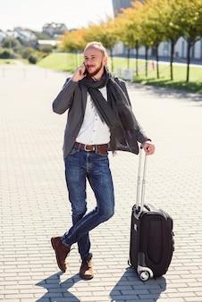 Sukcesy biznesmen w swobodnym garniturze wyciąga walizkę, śpieszy na lotnisko i rozmawia przez telefon. młody caucasian mężczyzna iść w podróż służbową.