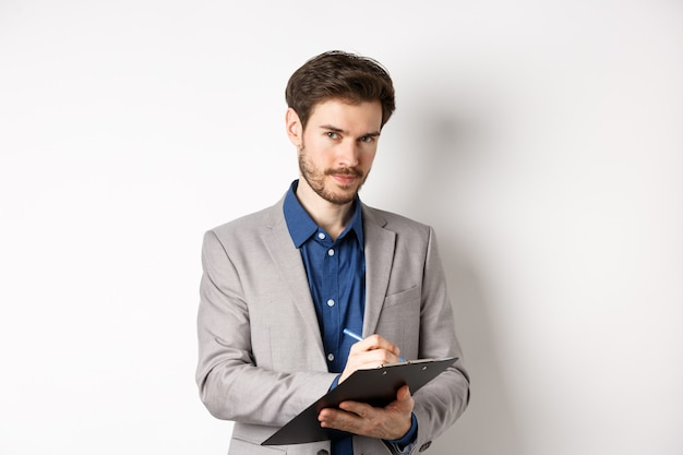 Sukcesy biznesmen w szarym garniturze robienia notatek, pracujący w odzieży biurowej