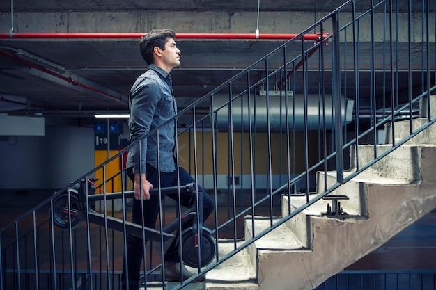 Sukcesy biznesmen wchodzenie po schodach budynku idzie do pracy, trzymając skuter elektryczny do dojazdów do pracy