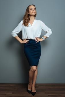 Sukcesy bizneswoman. atrakcyjna magnetyczna przyjemna kobieta stojąca na szarym tle i pokazująca swoją pewność siebie podczas pracy w biznesie