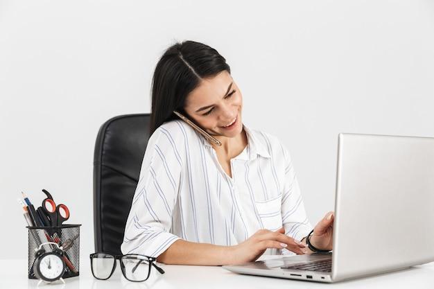 Sukcesy bizneswoman brunetka mówiąc na smartfonie siedząc przy stole i pracując na laptopie w biurze na białym tle nad białą ścianą