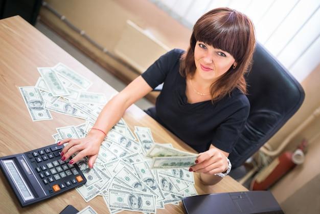 Sukcesy bizneswoman przy biurku oferuje i trzyma pieniądze na łapówkę.