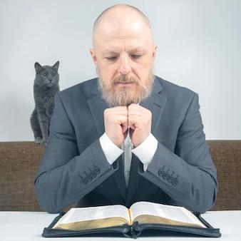 Sukcesy brodaty biznesmen modlący się i badacz biblii