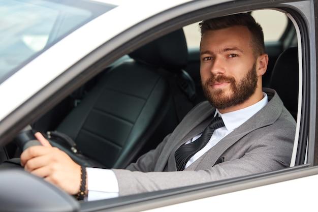 Sukcesy kaukaski mężczyzna w formalnym garniturze podczas prowadzenia samochodu
