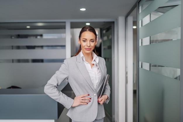 Sukcesy kaukaski młody bizneswoman stojący wewnątrz firmy, trzymając rękę na biodrze, aw drugiej ręce trzymając tablet.
