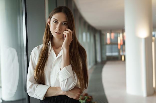 Sukcesy młoda bizneswoman, stojąca w pobliżu okna na korytarzu biura i patrząc kamery.