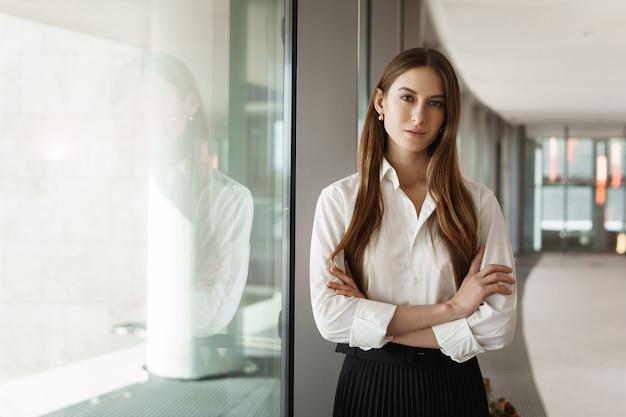 Sukcesy młoda bizneswoman, stojąca w pobliżu okna na korytarzu biura, uśmiechnięta i patrząc na kamery.
