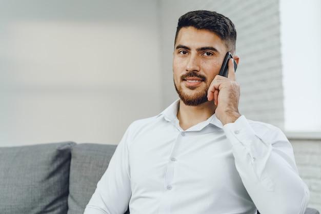 Sukcesy młody biznesmen rozmawia przez telefon