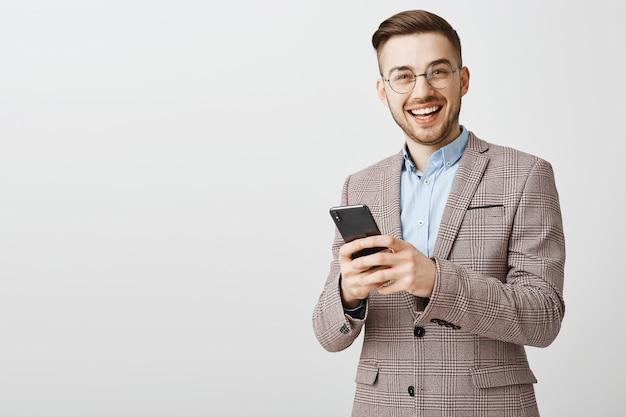 Sukcesy młody przedsiębiorca mężczyzna wysyłający sms-y, wysyłający wiadomości ze smartfona