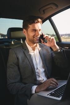 Sukcesy reżyser mężczyzna w garniturze rozmawia na smartfonie i pracuje na laptopie, siedząc z powrotem w samochodzie klasy biznes