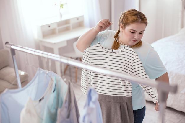 Sukienka marzeń. tęga młoda kobieta stojąca w pobliżu wieszaka na ubrania podczas przymierzania nowej sukienki