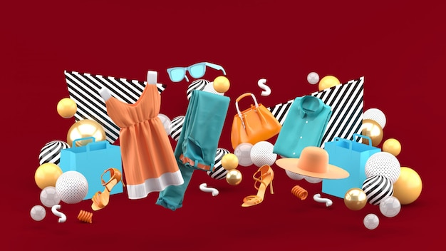 Sukienki, spodnie, bluzy, czapki, torebki, szpilki i okulary przeciwsłoneczne wśród kolorowych piłeczek na czerwono. renderowania 3d.