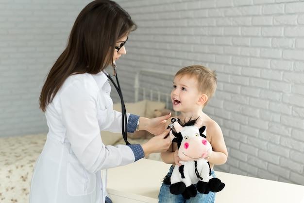 Suknia lekarza słucha dźwięku płuc i serca dziecka pacjenta ze stetoskopem