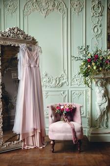 Suknia ślubna i bukiet panny młodej w pięknym wnętrzu