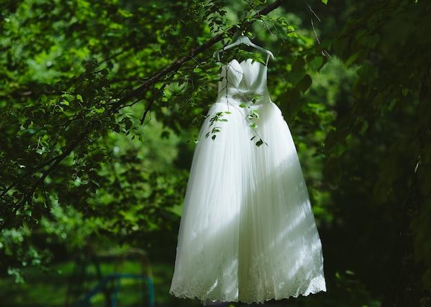 Suknia ślubna wisząca na drzewie w parku