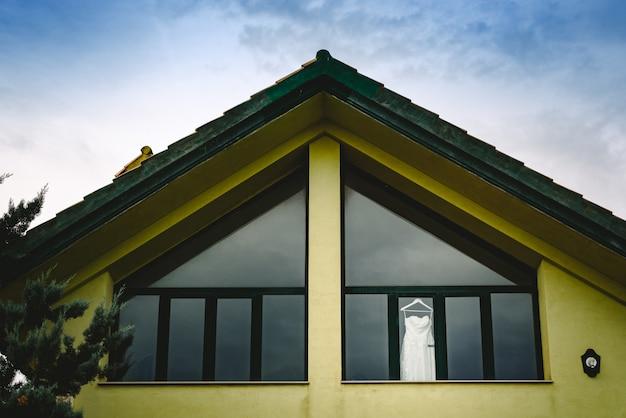 Suknia ślubna zwisająca z okna widziana z zewnątrz w intensywnym błękitnym niebie.
