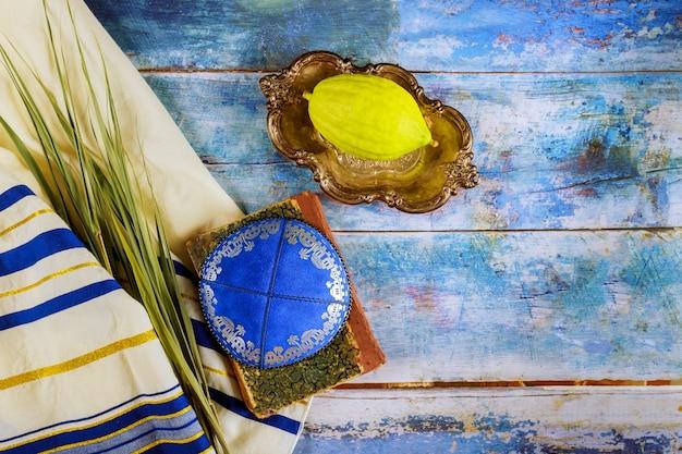 Sukot żydowski festiwal tradycyjnego symbolu religijnego etrog, lulav, hadas, arava kippah tallit modląca się książka