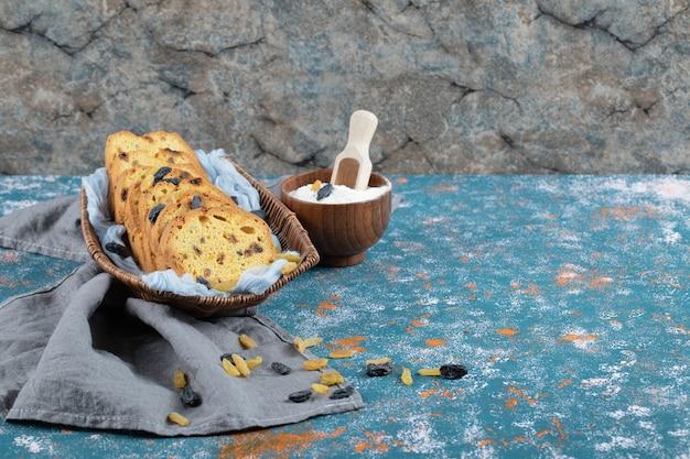 Sultana ciasto plastry w drewnianej tacy na niebieskim ręczniku