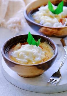 Suma bubura. jawajska owsianka deserowa z mąki ryżowej, mleko kokosowe z syropem z cukru palmowego. podawany w drewnianej misce. popularna przystawka do przełamywania postu podczas ramadanu.