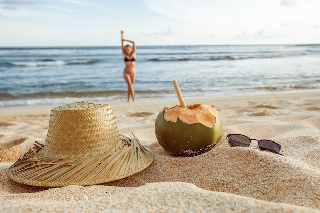 Summer girl w rozmazaniu z oceanu na piasku leży jej kapelusz, okulary przeciwsłoneczne i kokos