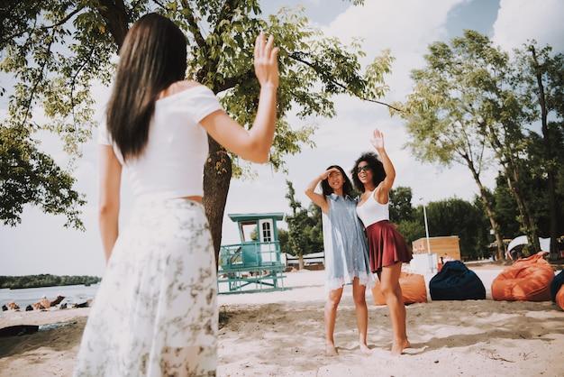Summer leisure multiracial women on sunny beach.