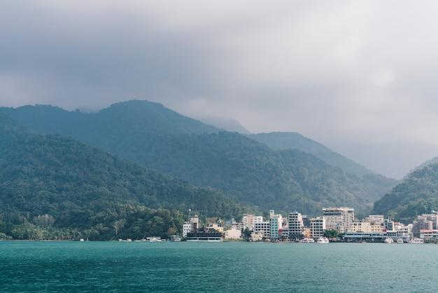 Sun moon lake z mglistą górą, shuishe pier i budynkami