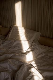 Sunbeam pada na łóżko. promienie słońca przez okno rano. nowy dzień z rozbłyskiem ciepłego słońca.