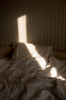 Sunbeam pada na łóżko. promienie słońca wpadające przez okno w godzinach porannych. nowy dzień z rozbłyskiem ciepłego słońca.